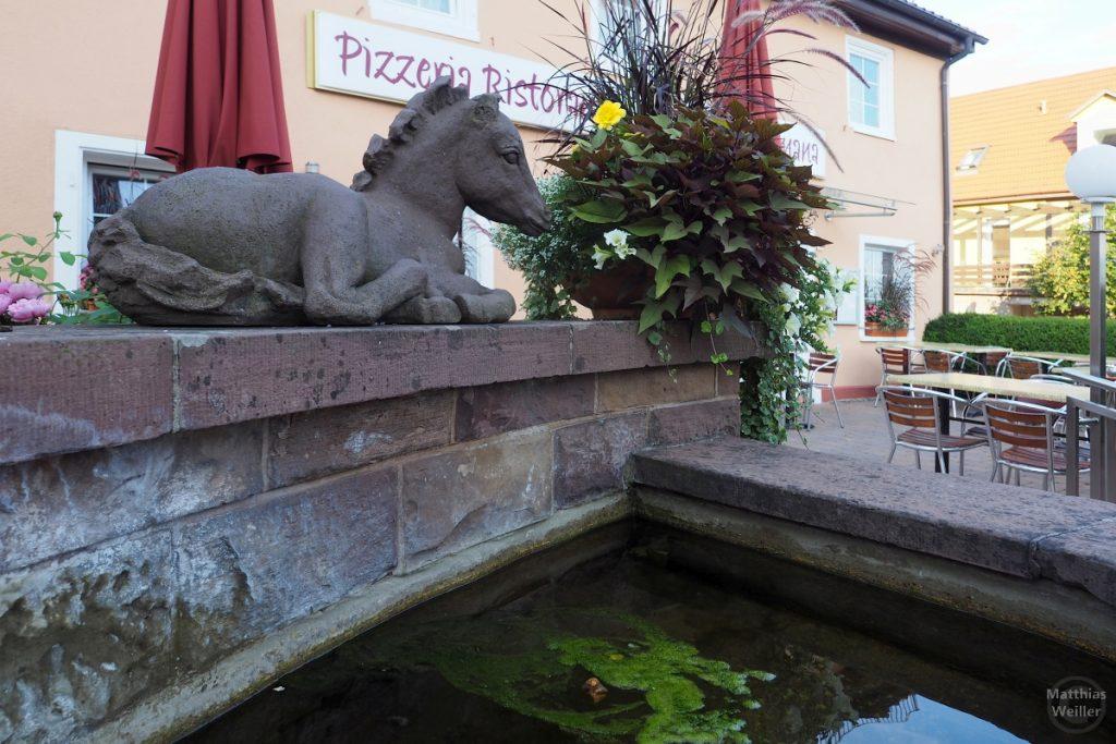Liegende Pferdskultpr auf Sandsteinbrunnen für Pizzeria/Osteria Romana in Sternenfels