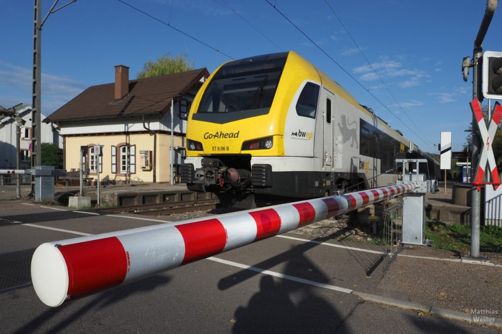 """Schranke rot-wei´ß mit fahrendem Zu """"Go-Ahead/bwegt"""" gelb-weiß und Bahnhof Kleinsteinbach"""