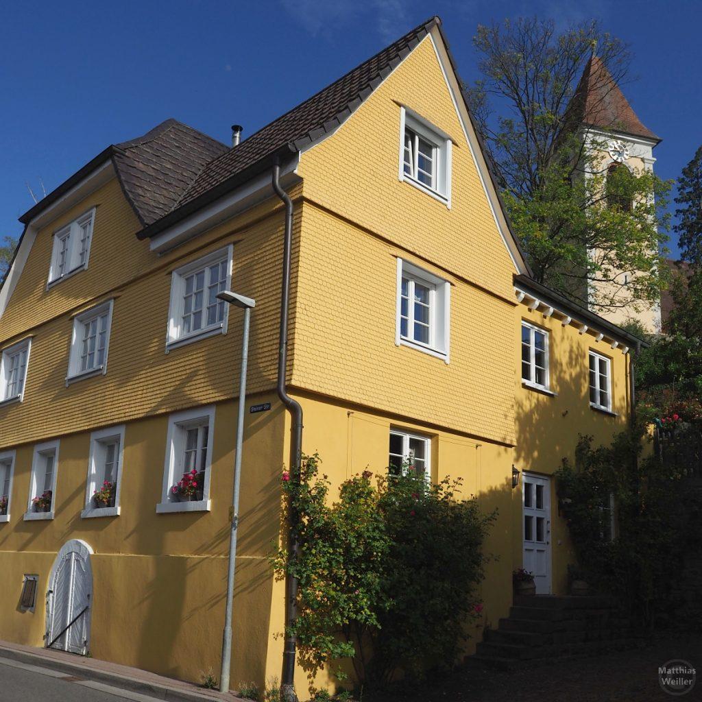 Getaältes, gelbes Künstlerhaus vor Kirche und unter blauem Himmel in Königsbach, Pfinztal