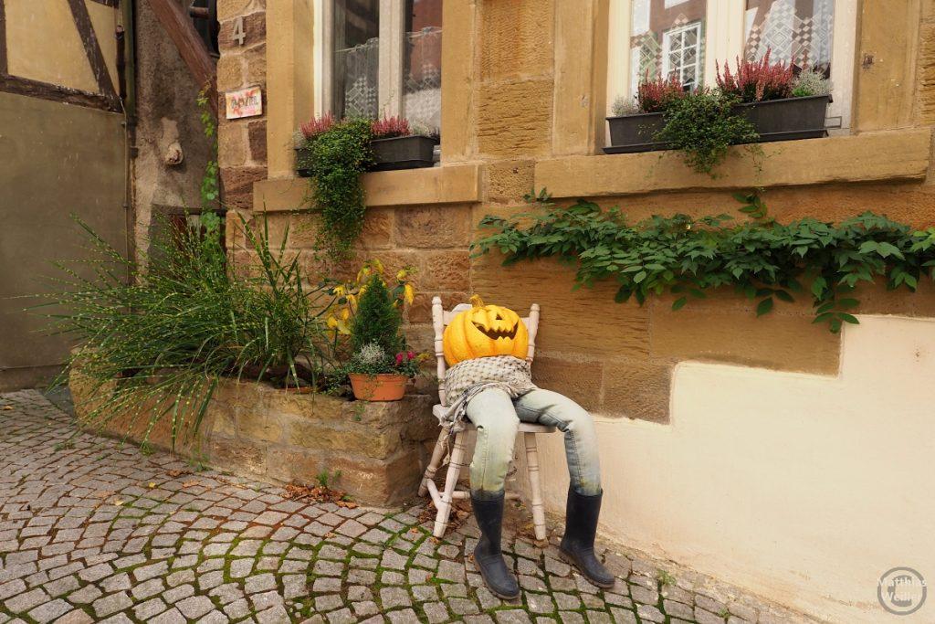 Unterleib-Dummie mit Kürbiskopfmaske im Stuhl vor Haus