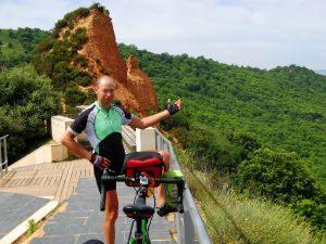 Selbstporträt mit Rad vor rotem Fels, Las Medulas, grün/rot