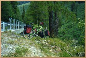 Laärchengrün mit LEitplanke, grünem Velo und rot-schwarzen Packtaschen