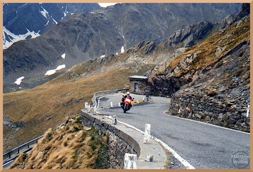 Serpentine Gaviapass mit Motorrad und Velofahrer, braunes Gras, Felsgeröll, Schneereste