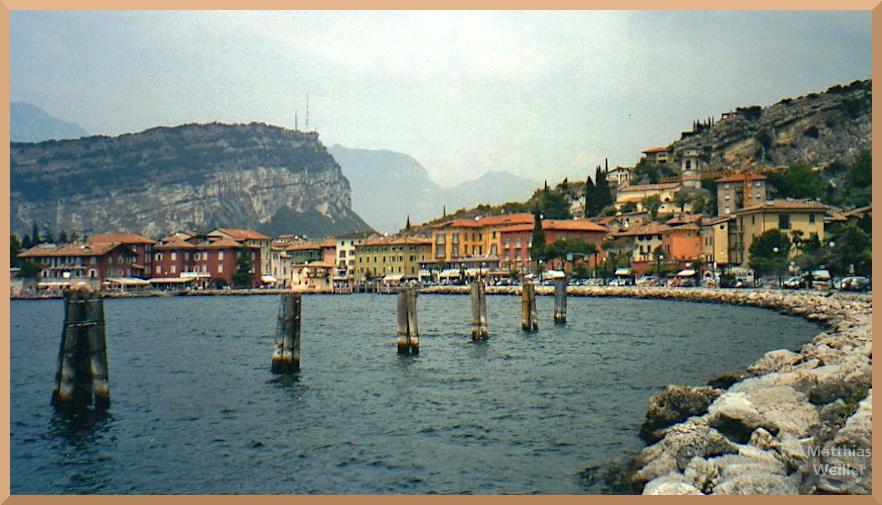 Gardasee-Bucht mit Torbole, rötliche Fassaden, Steinbrockenufer