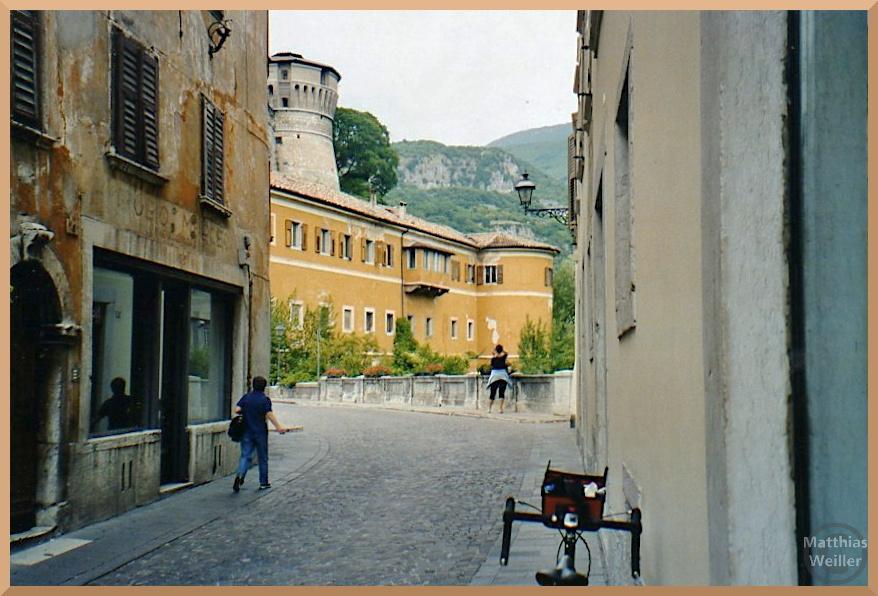 Ockerfarbenes Schloss mit Festungsturm darüber aus Pflasterasse vor Brücke betrachtet, Rovereto
