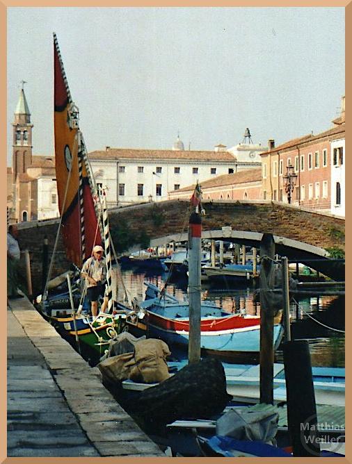 Barke mit buntem Segel vor Kanalbrücke und spitzem Kirchturm in Chióggia