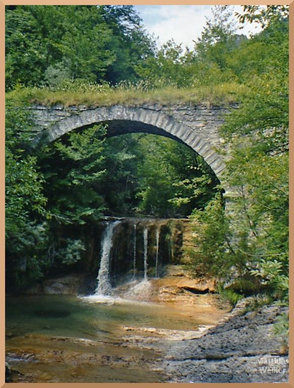 romantischer Wasserfall unter grün bewachsener Steinbogenbrück mit Badegumpe