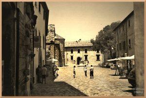 gepflegte Pflaster auf der Piazza San Leo mit dezentem Besuchercharme, sepiafarben