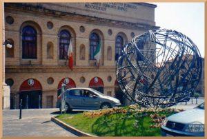 stählerne Wetlkugel auf Verkehsinsel vor Oper von Macerata