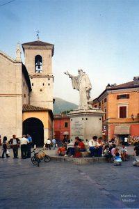 belebte Piazza mit handweisender Skulptur San Benedetto, Nórcia