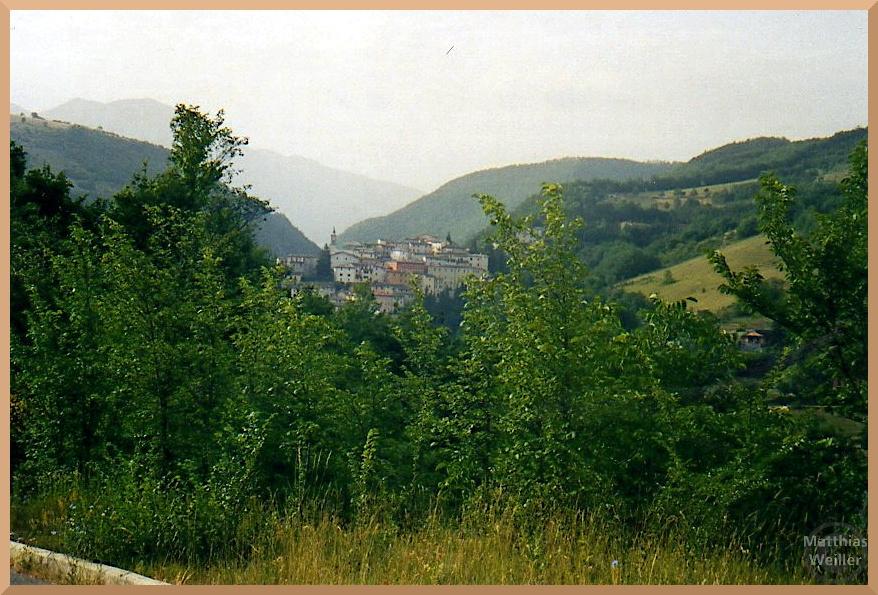 Prci in der Totalen, Hügelstadt deingebunden in Berge im Hintergrund, durch grünen Bewuchs betrachtet