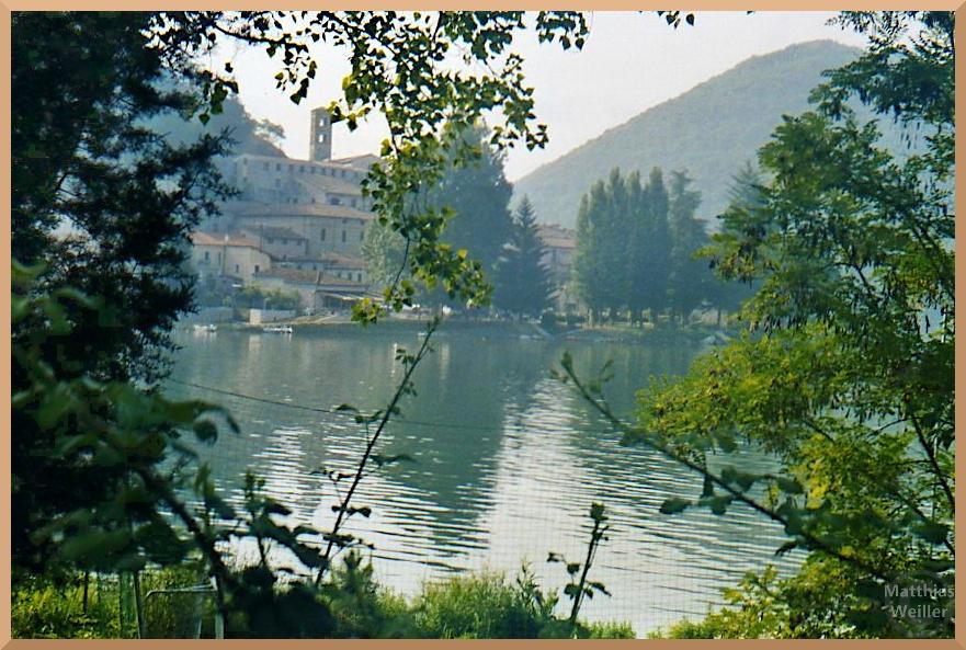 Ortskulisse vor Lago di Piediluco durch Buschfenster, grünliche Tönung