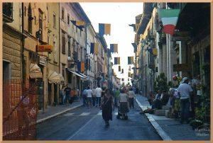 Fußgängerstraße in Leonessa in Festbeflaggung zum Mittelalterfest, blau-gelb Fahnen über der Straße