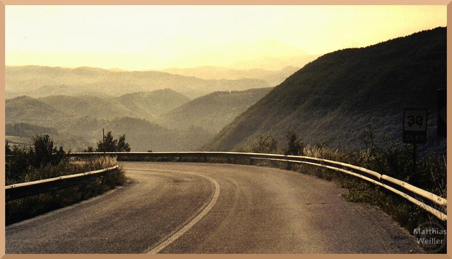 Straßenkurve mit Leitplanke über endloser Hügelkette zwischen Albaneto und Posta, sepiafarben