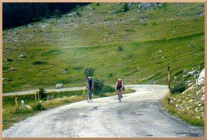 zwei Rennradler auf Kurvenaanstieg am Valico Capo la Serra, grüne Hänge mit weißem Findelfels