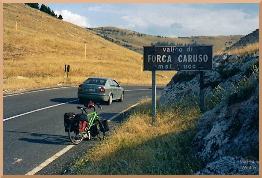 braungebrannte Wiesenhügel am Forca Caruso mit Passschild, Velo und Auto