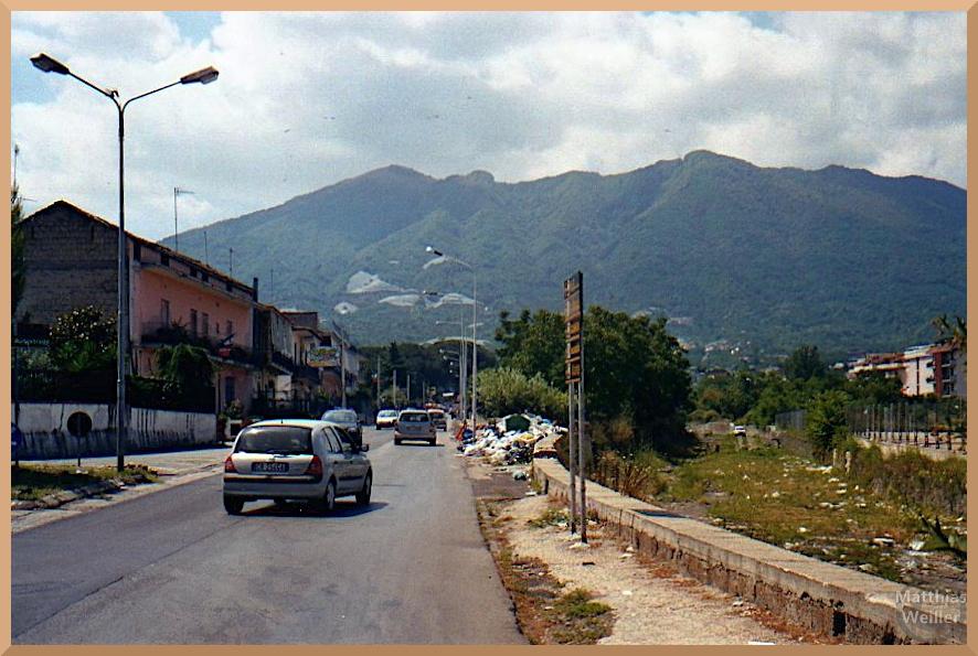 Straße mit Autos und Müll, Somma, Vesuv im Hintergrund