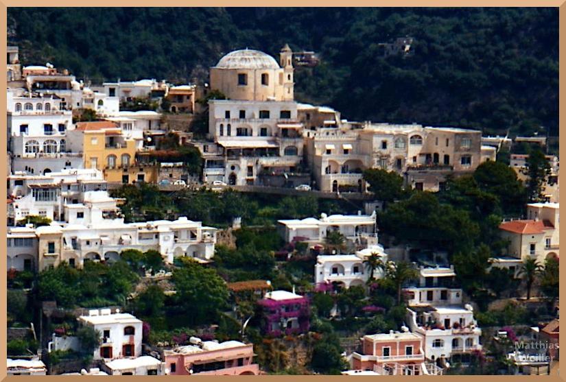 Frontansicht von Positano mit Kuppelbau, grün/weinroter Bewuchs zwischen und an Häusern, weiße Fassaden