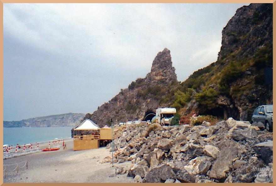 spitzer Felszapfen mit Tunnel und Strand an Küste, Capo Grosso