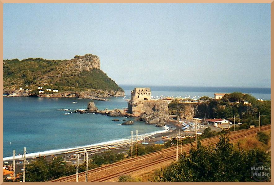 Eisenbahntrasse vor Meer mit Festung an Spitzbucht, Strand, Booten und Felsinsel gegenüberliegend