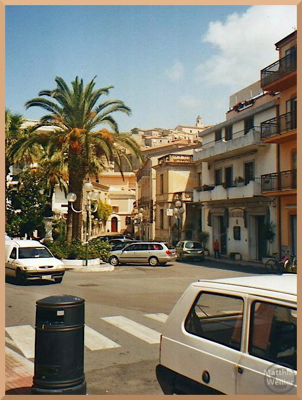 Scalea, aufsteigendes Stadtbild mit Auto und Palme im Vordergrund