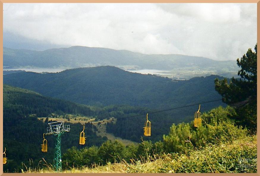 Sesselift mit gelben Käfigen am Monte Donato, Panorma mit See in der Ferne
