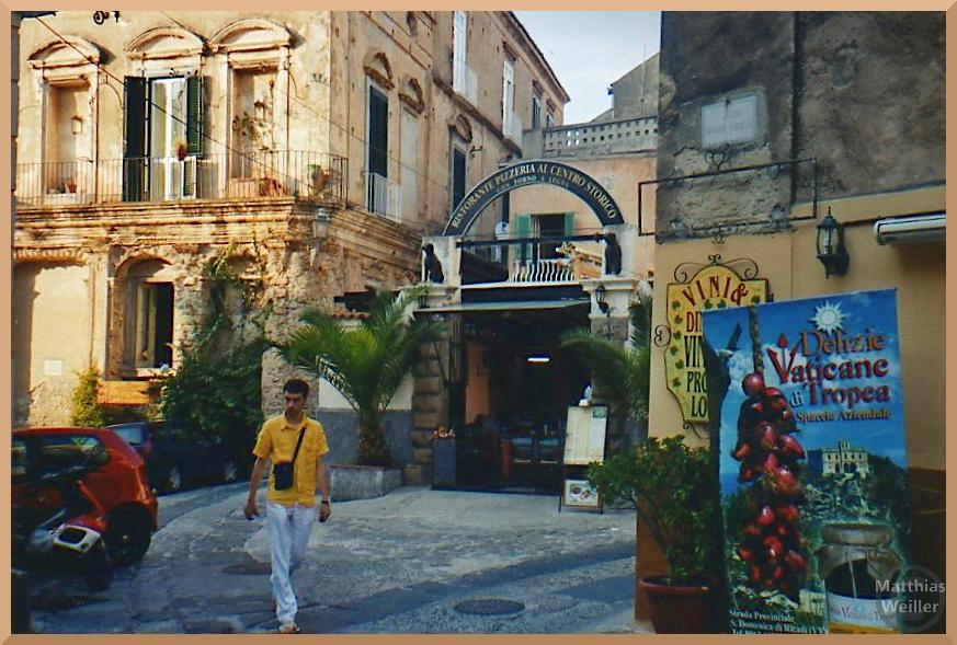 Tropea, gelbliche Fassaden mit Mann und Rote-Zwiebel-Plakat