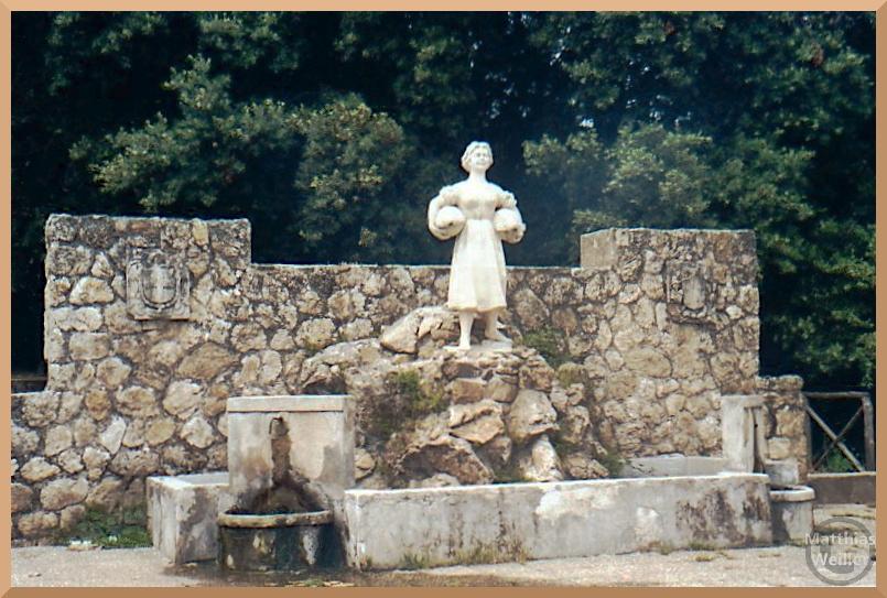 großer Brunnen mit Mauer und Frauenfigur mit 2 Tonkrügen