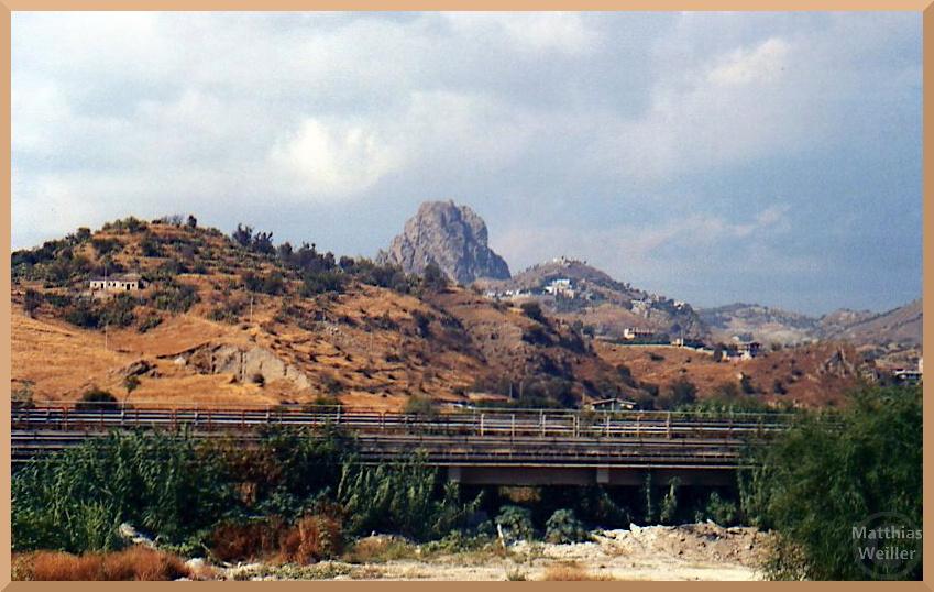 Felsen mit altgriechischen Dörfern, Mélito di Porto Salvo, Straße und braungedörrter Hügel im Vordergrund