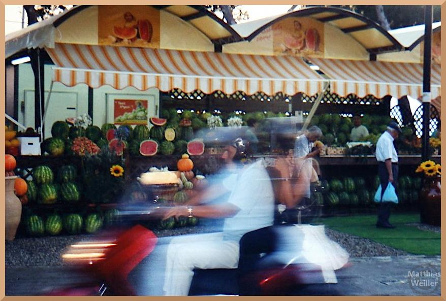 Melonenstand mit Vespa-Fahrer durchfahrend im Bild, Reggio di Calábria