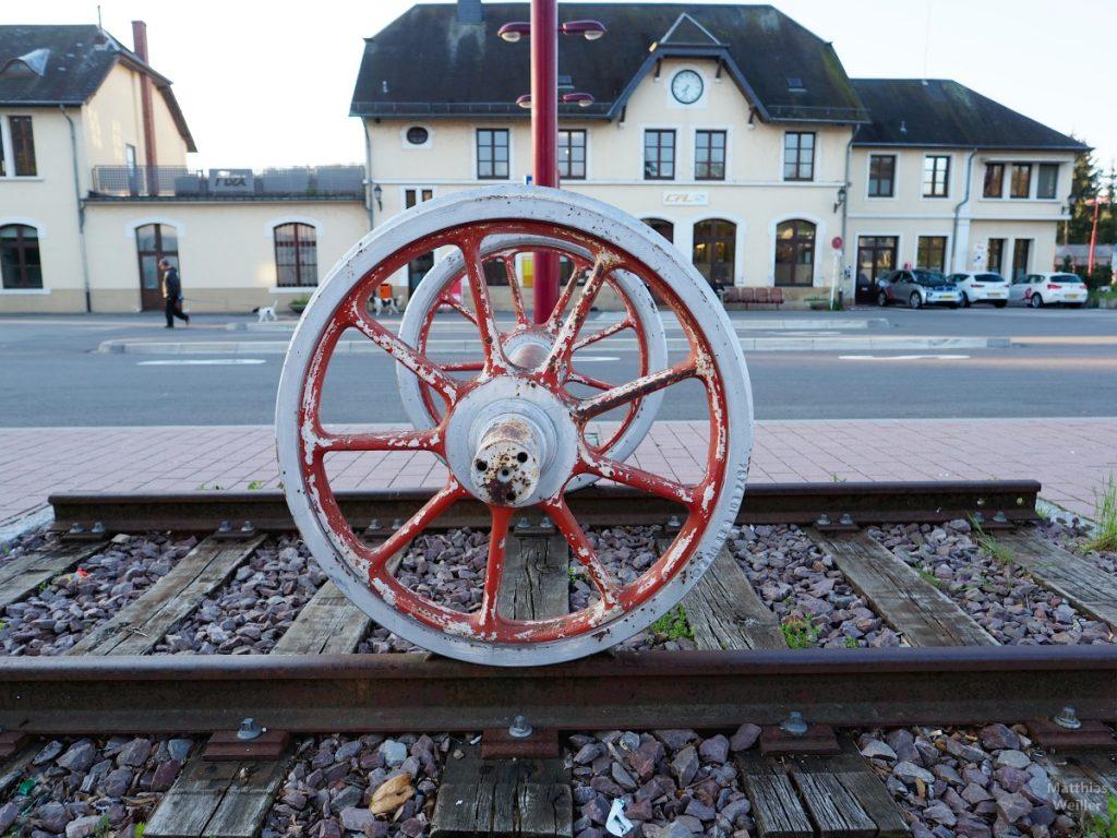 Nahaufnahme Skulptur aus Schienstück und Eisenbahnrad vro Bahnhof Wasserbillig