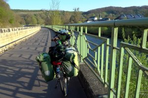 Sauerradweg mit grünem Geländer, grünes Velo, Lansgur gegenüber, von Geländer teils verdeckt