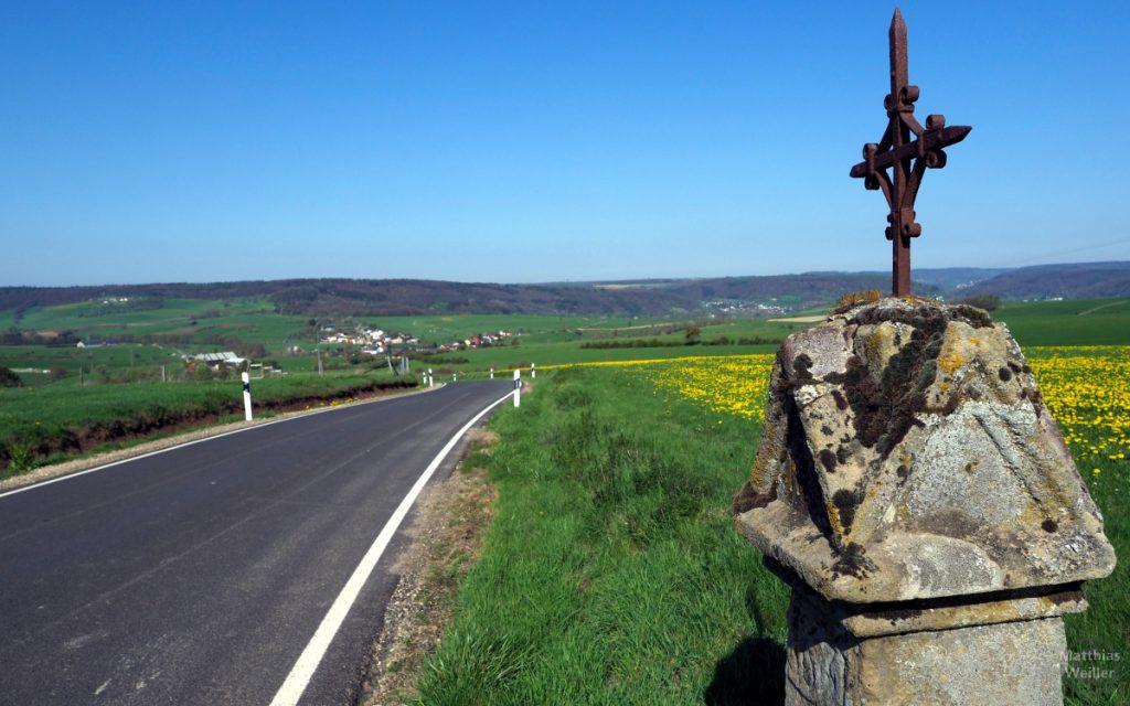 Steinsäule mit rostigem Kreuz, weites Panorama auf Hügelland mit Löwenzahnwiese