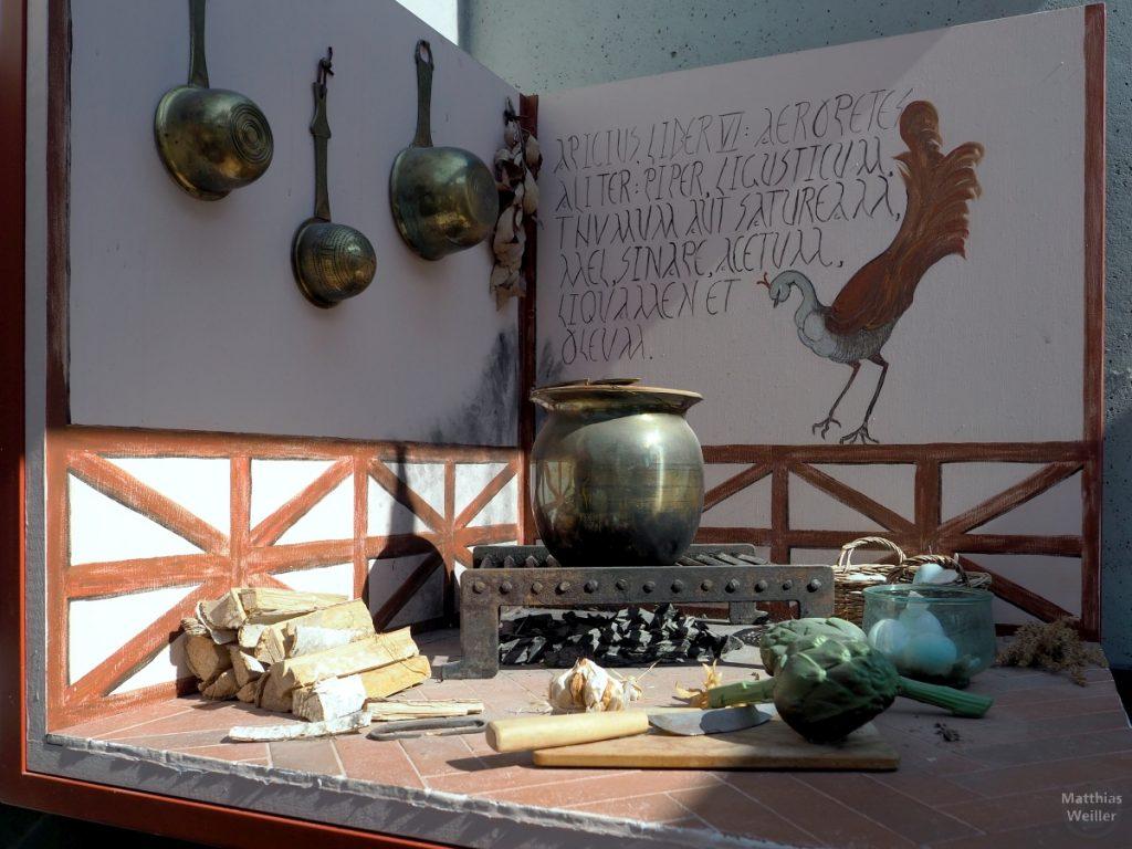 Römische Kochstelle mit Kupfertöpfen, Artischocke, Holzscheiten, Vogelmalerei