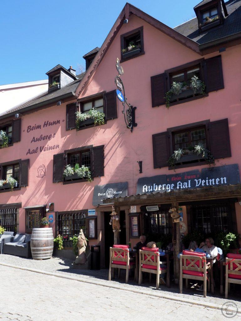 """pastell rotweinfarbene Fassade mit Bestuhlung der Auberge """"Beim Hunn"""", Vianden"""
