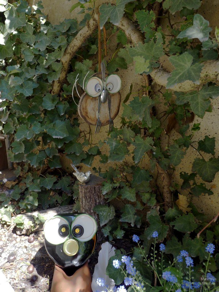 Eulenaus Konservendeckeln, Gabeln, Holzscheiben vor Efeu