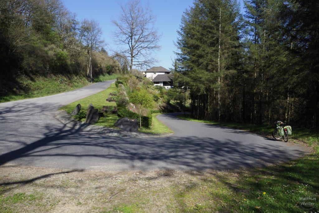 Serpentine mit Velo und Haus im Hintergrund, Abfahrt nach Untereisenbach