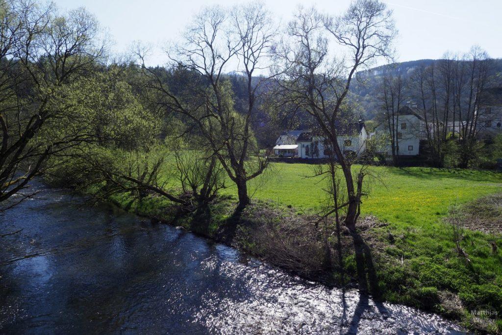 leicht glitzernde Our mit Uferbewuchs, Auenwiesen und versteckten Häusern, Obereisenbach