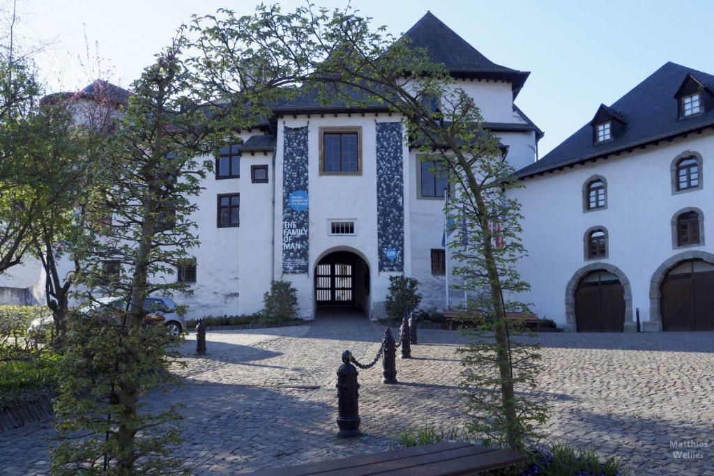 Schloss Clervaux mit Platz durch Baumtorbogen betrachtet