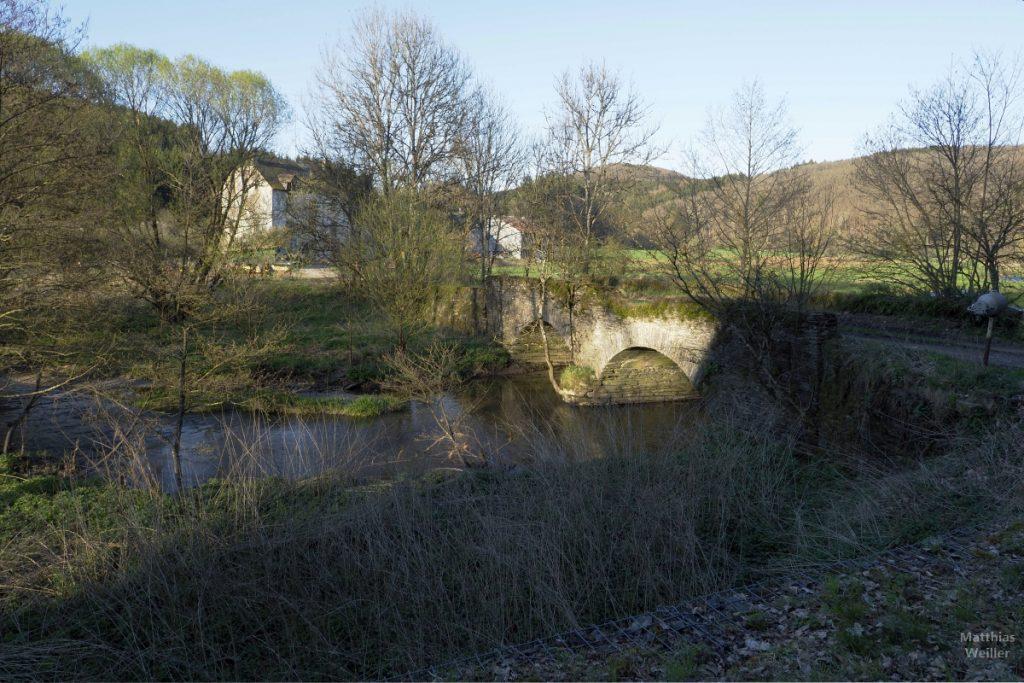 Doppelsteinbockbrücke, Bauernhäuser hinter Bäumen versteckt, in verträumter Abendsonne an der Clerve