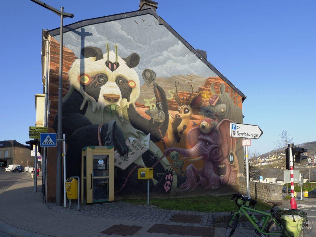 Fassadenmalerei in Wiltz, comicähnliche Tiere (Panda, rosa Elefant, Nashorn, Reh) mit Telefonzelle davor
