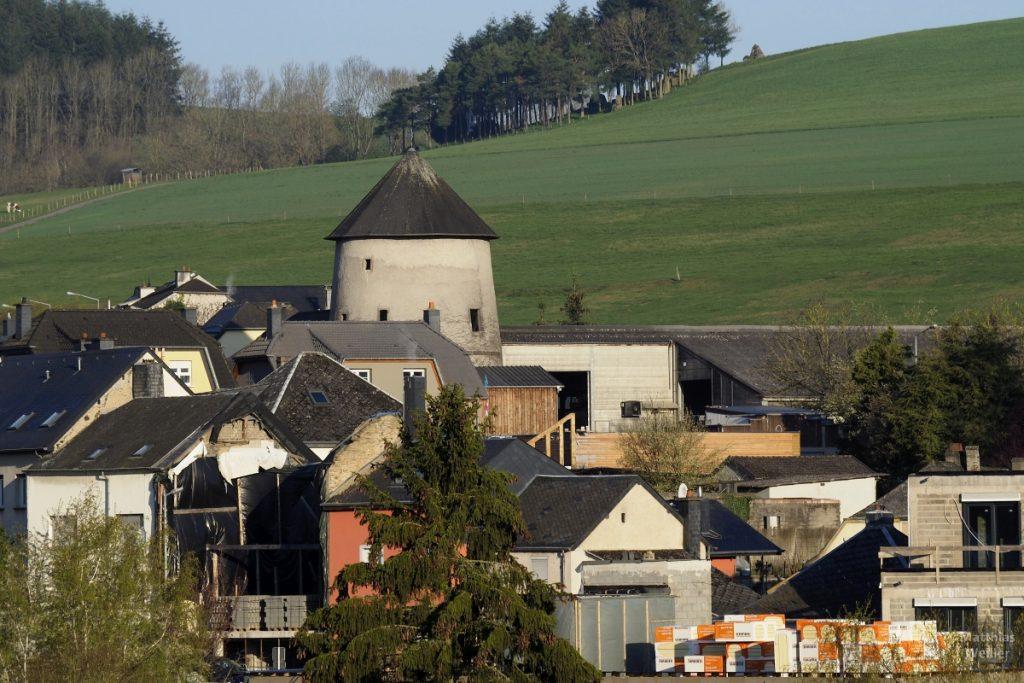 Rund-/Kegelturm in bäuerlicher Siedlung vor grünem Hügelhang