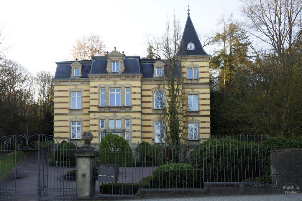Villa mit Spitzturm in Wiltz gelbe Fassade mit roten Sandsteinstreifen quer