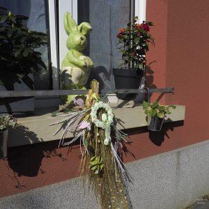 hellgrüner Osterhase in Fenster mit diversem Blumenschmuck