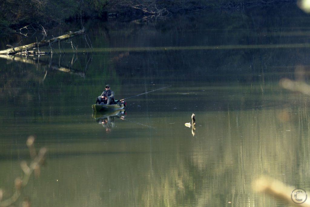 Angler in Kahn, Totelhol im Wasserspiegel