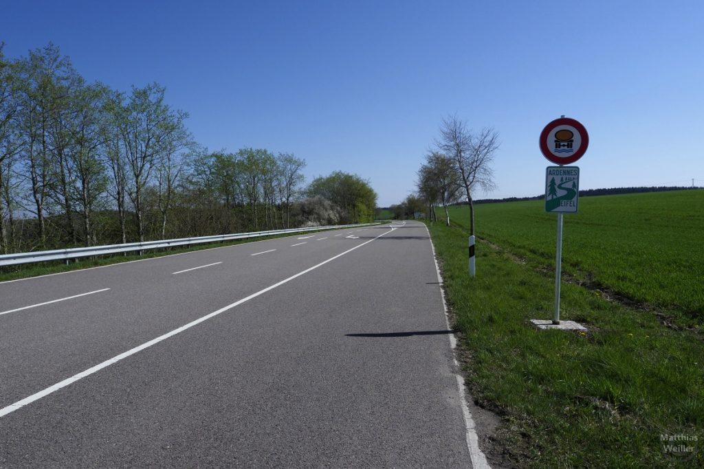 """Straßenperspektive mit Schild """"wasserschutzgebiet"""" und Touristenschild grün/weiß """"Ardennes/Eifel, geschungene Straße und Baumsymbole"""
