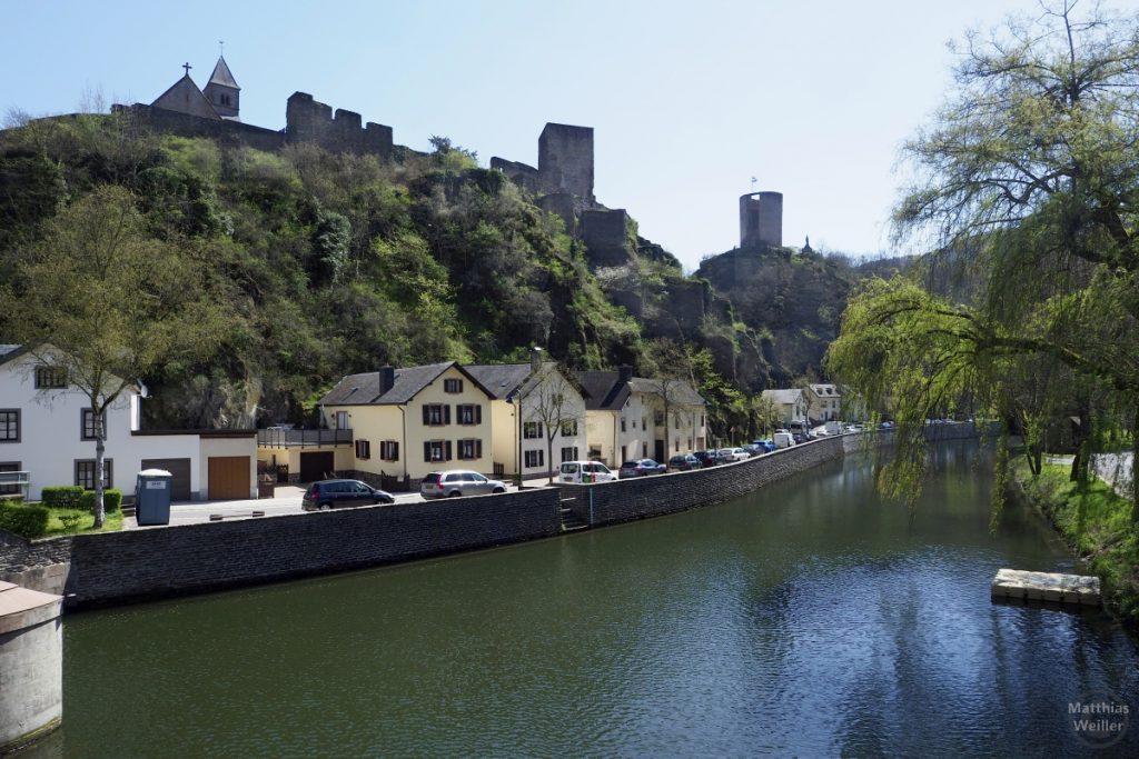 Burgansicht von unten mit Sauer und Häusermeile am Fluss in Esch-sur-Sûre