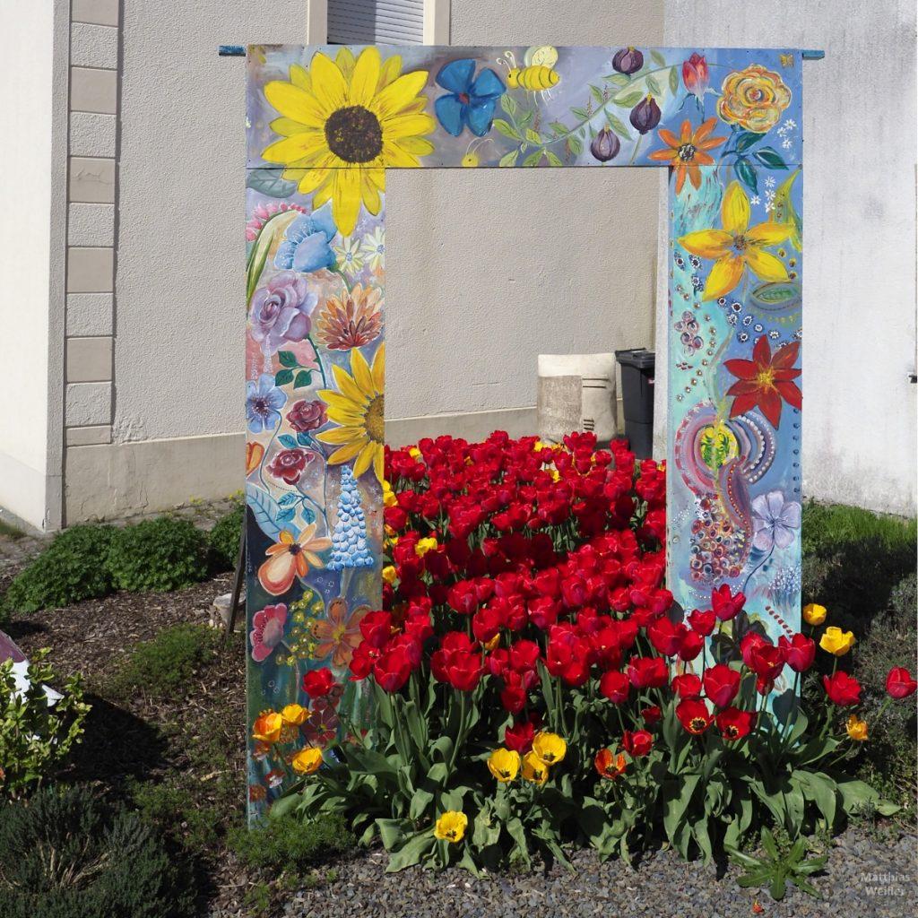 eckiges Blumentor bunt gemalt mit roten Tulpen darunter