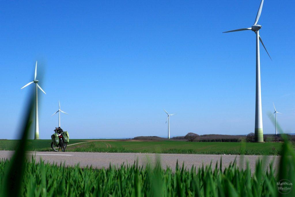 Windräder mit grünen Sockel, grünes Velo, Bodenperspektive mit weichgezeichnetem Grüngras davor