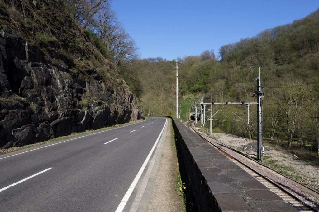 Straße neben Fels und Bahnlinie mit Tunnel zur anderen Seite